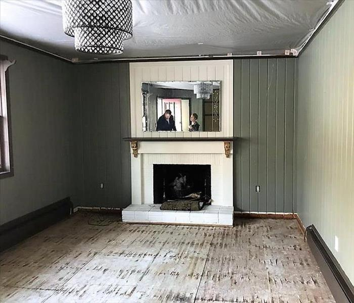 dining room with fireplace with water damage the floors removed and ceiling sagging