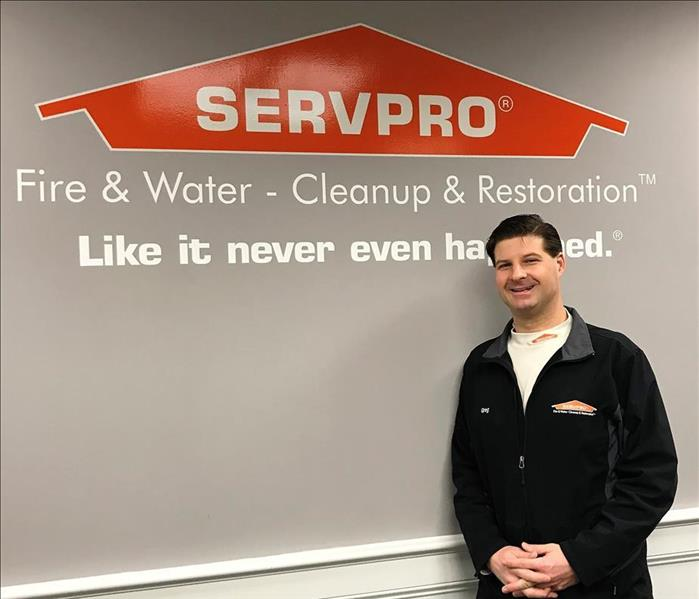 man standing in front of a servpro sign