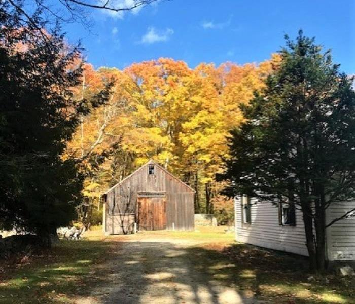 an old barn with dirt driveway, trees with bright yellow and orange leaves and a blue sky