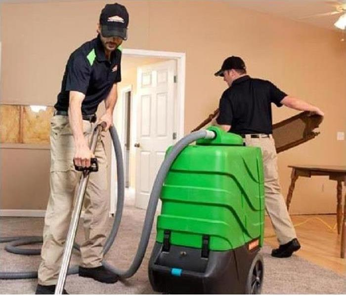 men in servpro uniforms vaccuming