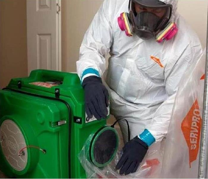 Man with protective suit on and respirator cleaning the air in a home