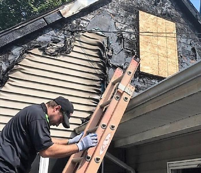 Man climbing down a ladder of a house with melted siding and wood over the window