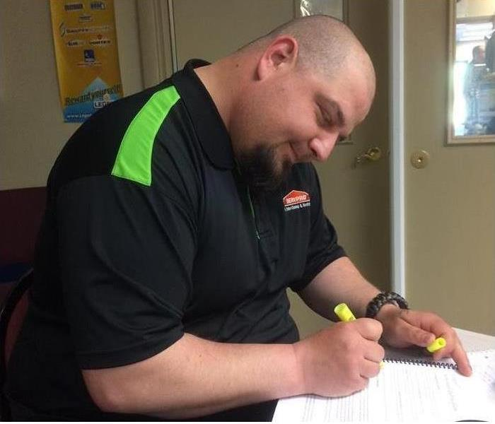 man in Servpro shirt sitting at a desk in a training class